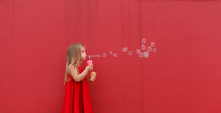 Blond girl child in red dress on a background of the  wall blows bubbles. Blond girl child in red dress on a background of the red wall blows bubbles Royalty Free Stock Photos