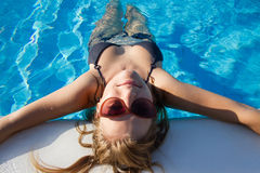 Blond girl chilling in the pool Stock Photo