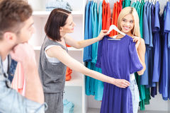 Blond girl choosing clothes in store. Young women is trying on new dress in boutique. She is looking at her boyfriend questioningly and smiling. Shop assistant Stock Photography