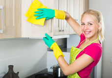 Blond girl cleaning surfaces at kitchen Stock Photos