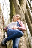 Blond girl climbing tree Stock Photos