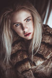 Blond girl with a cold stare. And full lips in a fur coat stock photography