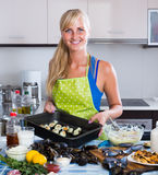 Blond girl cooking mussels croquettes in baking tray Royalty Free Stock Photos