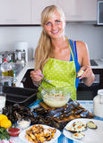 Blond girl cooking mussels croquettes in baking tray Stock Photo