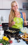 Blond girl cooking mussels croquettes in baking tray Stock Photography