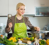 Blond girl cooking with vegetables. Portrait of blond girl cooking with vegetables Stock Image