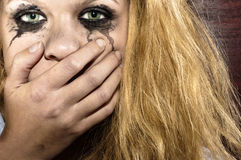 Blond girl covering her mouth. Against blurry background Stock Images
