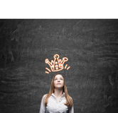 Blond girl with crown. Blond lady standing near blackboard with orange crown sketch on it. Concept of getting reward. Mock up stock photos