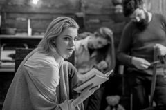 Blond girl with cunning eyes plotting something, conspiracy concept. Detective lover absorbed by favorite novel. Woman. In blue shirt, jeans and beige poncho royalty free stock photography