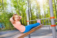 Blond girl curls up on board at the sports ground Stock Photos