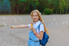 Blond girl with curly hairstyle in denim overalls happy smiling blows soap bubble royalty free stock photos