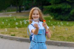Blond girl with curly hairstyle in denim overalls happy smiling blows soap bubble royalty free stock images