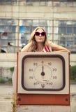 Blond girl on damaged gas station royalty free stock image