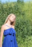 Blond girl in dark blue dress Royalty Free Stock Images