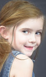 Blond girl  in denim. Cute blond girl with blue eyes looking over her shoulder Royalty Free Stock Photography