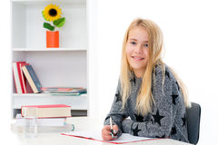 Blond girl doing homework Royalty Free Stock Photography