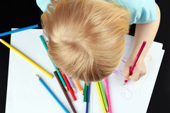 Blond girl is drawing by pencil Stock Images