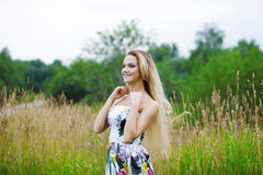 Blond girl in dress  on a meadow Royalty Free Stock Photography