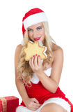 Blond girl dressed as Santa Claus. Beautiful blond girl  dressed as Santa Claus eating pandoro sliced Royalty Free Stock Images