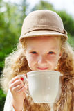 Blond girl drinking tea. Blond girl drinking cup of tea as refreshment in autumn Royalty Free Stock Photography