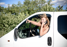 Blond girl driving car speaking on mobile phone. Picture of blond female driving car speaking on phone and looking out of window. Young woman excited and smiling Stock Photo