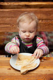 Blond girl eating delicious pancakes Royalty Free Stock Photography