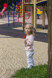 Blond girl eating piece of candy in park Royalty Free Stock Image