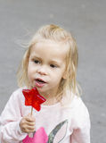 Blond girl eating piece of candy in park Stock Photography
