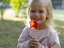Blond girl eating piece of candy in park Stock Photos