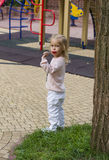 Blond girl eating piece of candy in park Royalty Free Stock Photo
