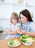 Blond girl eating vegetables with her mother Stock Image
