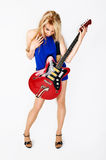 Blond girl with electric guitar. Beautiful blond girl with electric guitar on plain background stock photography