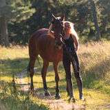 Blond girl embraces her horse Royalty Free Stock Photos