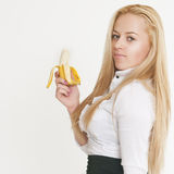 Blond girl enjoying a banana Stock Image