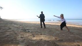 Blond girl chases leaving  bearded guitarist on beach at sunrise. Blond girl in evening dress chases leaving  bearded guitarist on beach at sunrise stock video