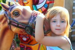 Blond girl with fairground horse enjoy in park Royalty Free Stock Photography
