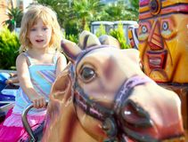 Blond girl with fairground horse enjoy in park. Outdoor Royalty Free Stock Photo