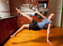 Blond girl falling in the kitchen Stock Photo