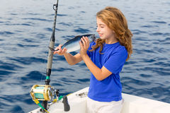 Blond girl fishing bluefin tuna trolling sea. Blond girl fishing bluefin tuna trolling in Mediterranean sea catch and release Royalty Free Stock Photos