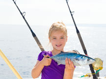 Blond girl fishing bonito Sarda tuna trolling  sea Royalty Free Stock Photos