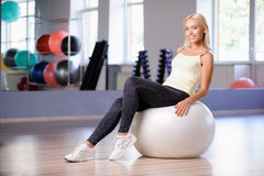 Blond girl with a fitness ball Royalty Free Stock Photography