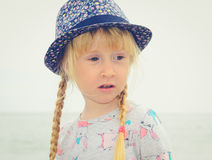Blond Girl with Floral Hat Looking Into Distance Stock Image