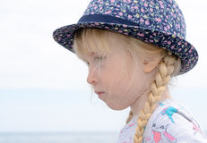 Blond Girl with Floral Hat Looking Into Distance Stock Photo