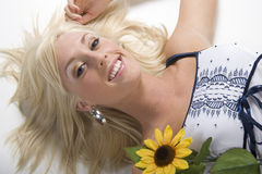 Blond girl with flower. Blonde girl lying on white background Royalty Free Stock Photography