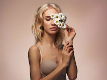 Blond girl with flower mask Stock Image