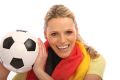 Blond girl with a football. Beautiful blond girl with a german flag holding a football royalty free stock images