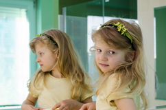 Blond girl in front of the mirror Stock Image