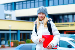 Blond girl in front of school building Stock Image