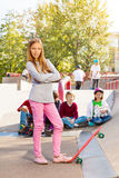 Blond girl in front with skateboard and friends Royalty Free Stock Photography