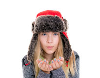 Blond girl with fur cap and scarf blowing in to the camera Royalty Free Stock Photography